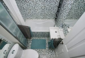 Really small bathroom showing toilet, sink, bath and shower.