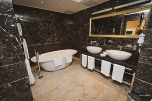 Ensuite with his and her sinks and a large soaking bath. Black tiles give this ensuite a romantic feel.